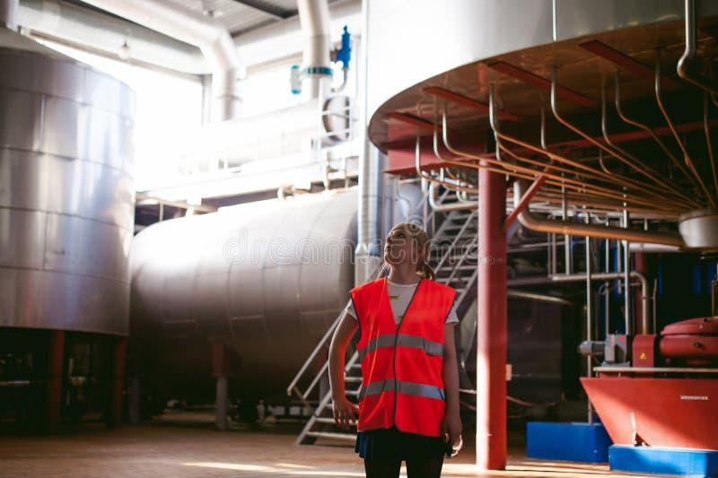 啤酒工厂的女工 长袍的画象妇女,站立在背景线食物生产,检查管理控制 免版税库存图片