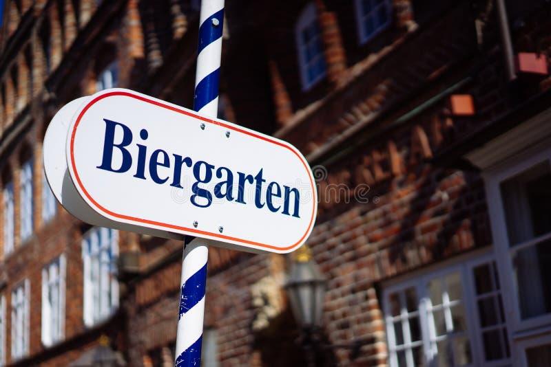 啤酒庭院标志 被打开的盾用德语biergarten一个晴朗的假日 老传统德国buildung在背景中 免版税图库摄影