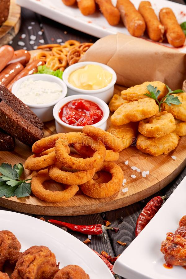 啤酒快餐关闭  烤香肠、矿块与洋葱圈和调味汁 库存图片