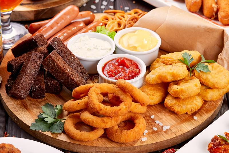 啤酒快餐关闭  烤香肠、矿块与洋葱圈和调味汁 免版税图库摄影