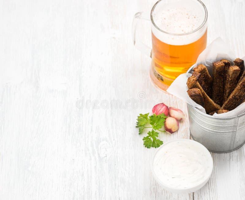 啤酒快餐集合 品脱在杯子的比尔森啤酒和黑麦面包油煎方型小面包片用大蒜乳脂干酪调味在老白色被绘 图库摄影