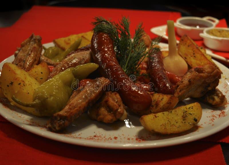 啤酒快餐-翼,香肠,土豆用调味汁 库存图片