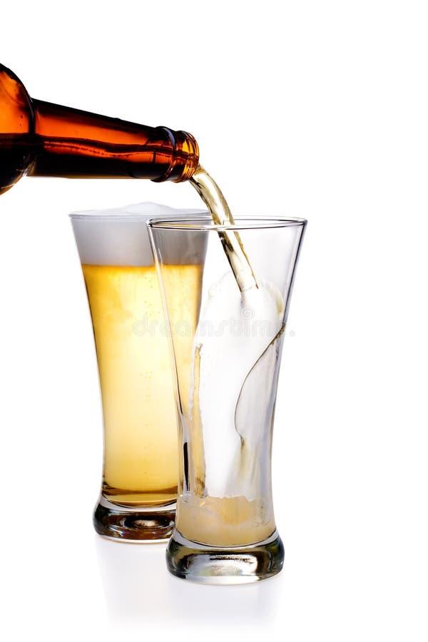 啤酒杯倾吐 免版税图库摄影