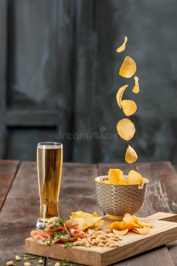 啤酒杯和土豆片,在白色的开心果 免版税库存图片