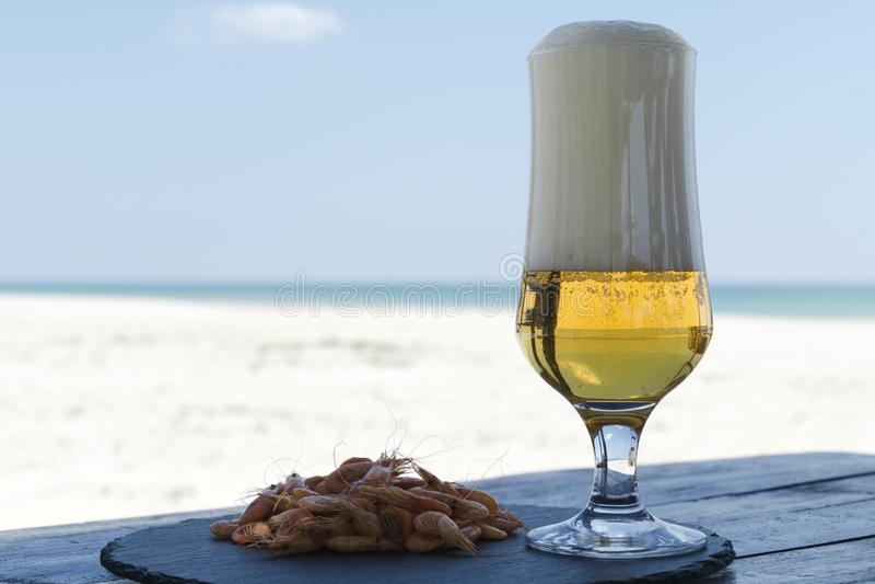 啤酒杯和虾在石板材在阴影桌里反对晴朗的海滩弄脏了海的背景 免版税库存图片