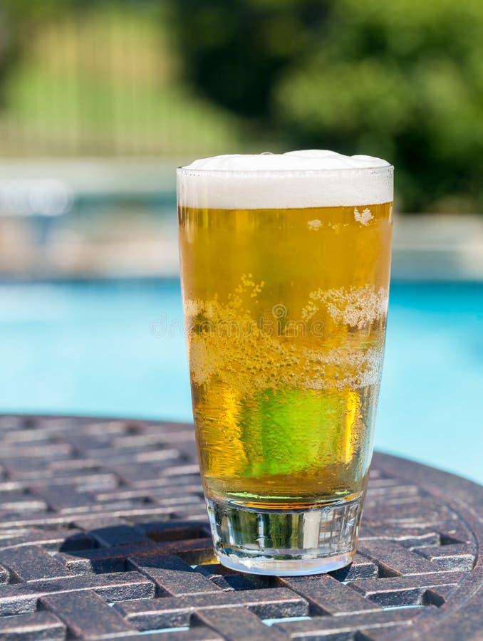啤酒杯游泳池边表 免版税图库摄影