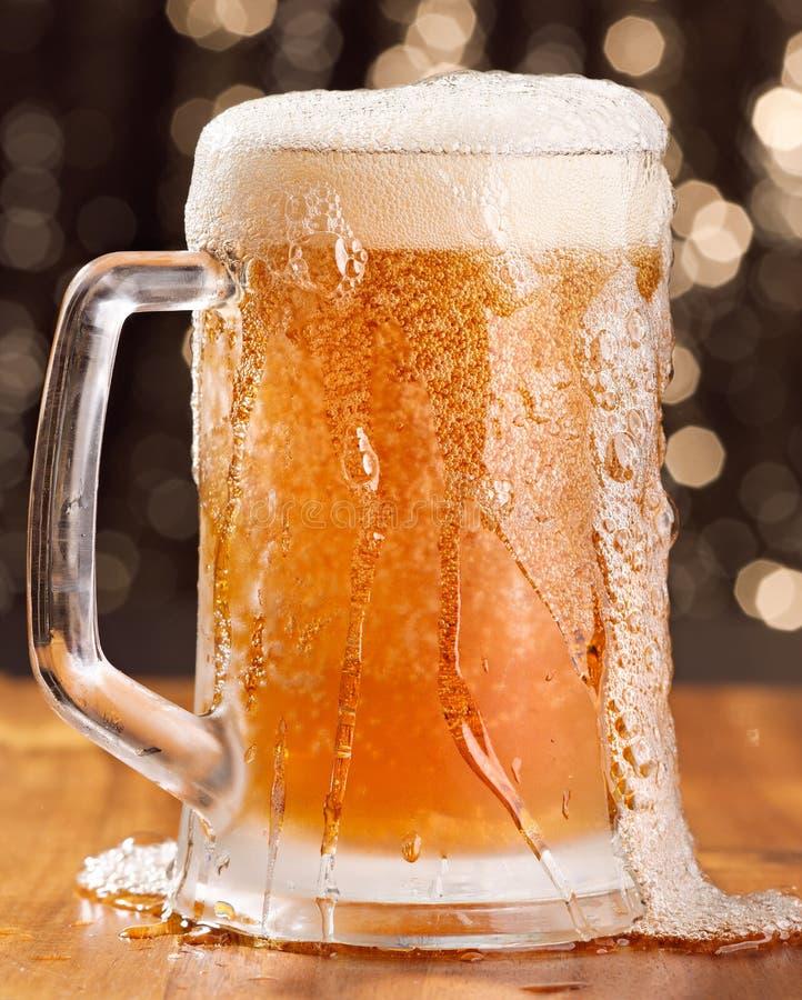 啤酒杯溢出 免版税库存图片