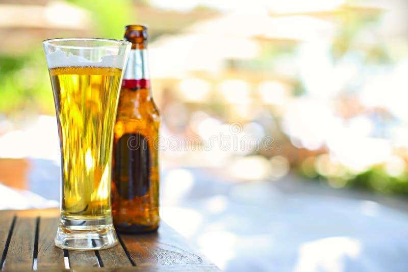 啤酒瓶和玻璃特写镜头视图在庭院里 免版税库存图片