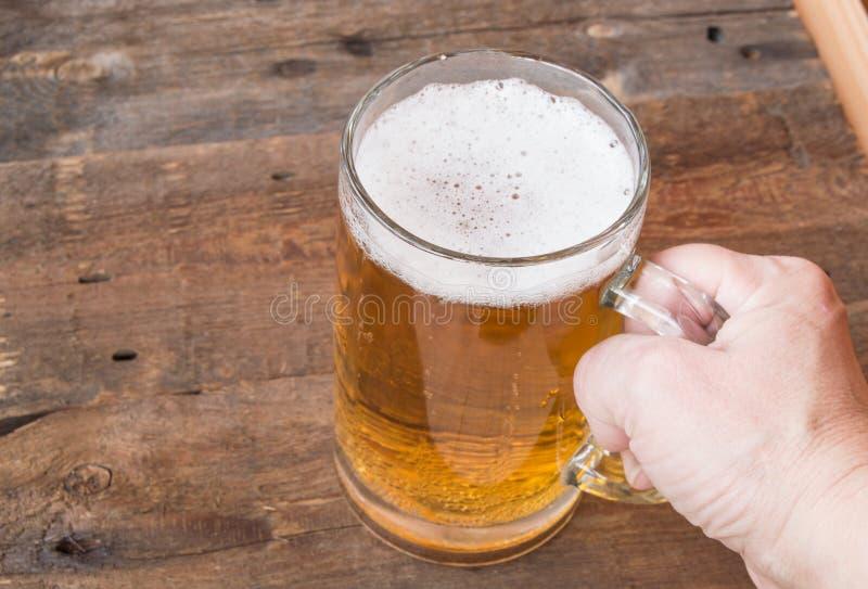 啤酒站立在老木背景的玻璃杯子,女性手举行 库存照片