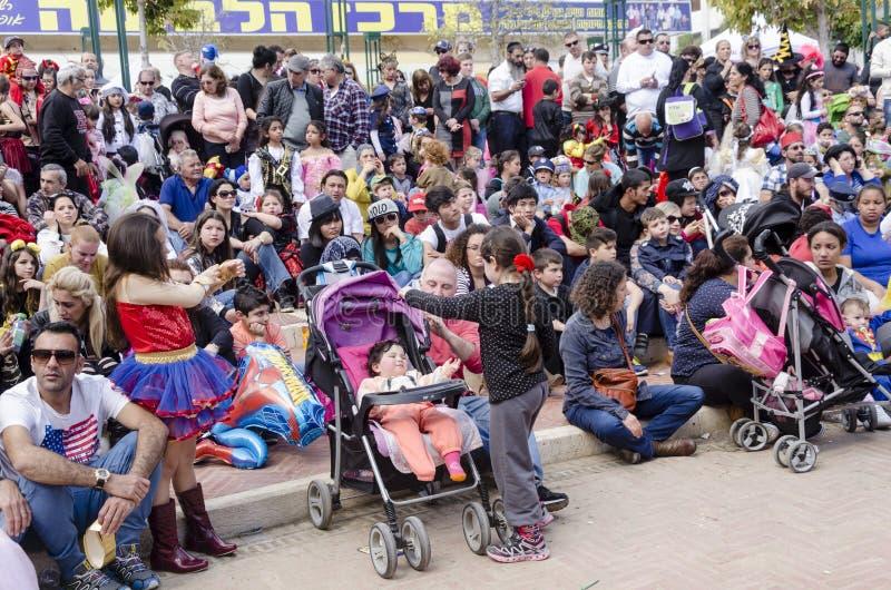 啤酒舍瓦,以色列- 2015年3月5日:有儿童观众的父母-坐并且观看在街道上的表现-普珥节 免版税库存图片