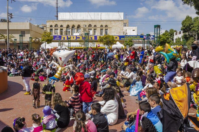 啤酒舍瓦,以色列- 2015年3月5日:狂欢节服装的孩子有他们的在街道上的父母的为庆祝普珥节 免版税库存图片