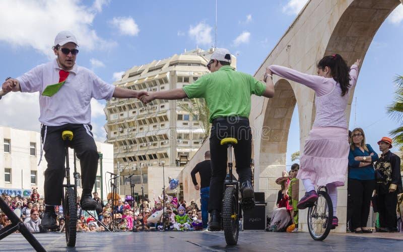 啤酒舍瓦,以色列- 2015年3月5日:男孩和女孩在自行车执行了与在街道场面的一个轮子-普珥节 免版税库存图片