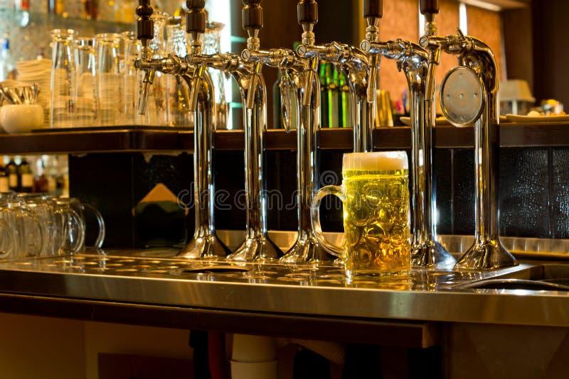 啤酒行在有啤酒大啤酒杯的一间客栈轻拍  图库摄影