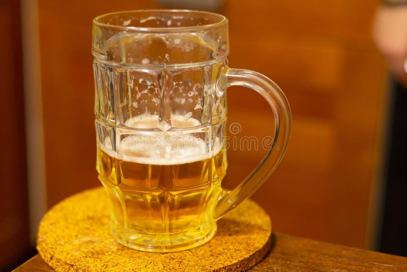 啤酒金黄蛇麻草醉酒的一半玻璃白色泡沫特写镜头客栈一份刷新的饮料 库存照片