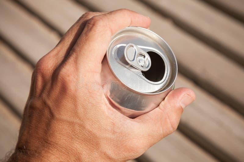 啤酒铝罐在一只男性手上 免版税库存图片