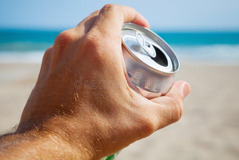 啤酒铝罐在男性手、海滩和海上 库存图片