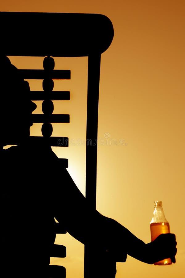 啤酒deckchair剪影日落 库存图片
