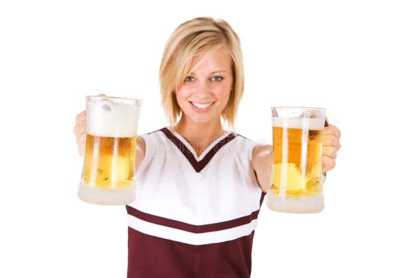 啦啦队员:提供两个玻璃杯子啤酒的妇女 库存照片