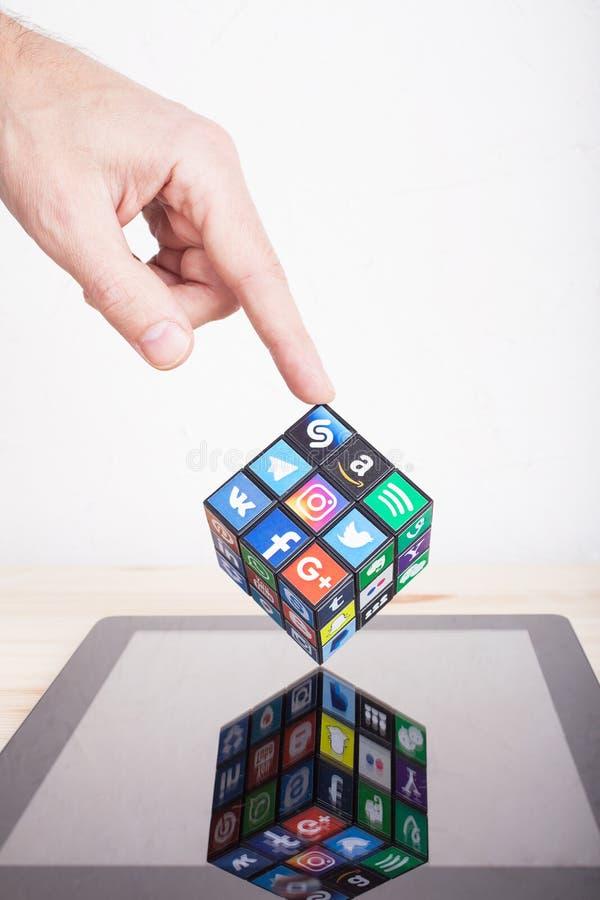 喀山,俄罗斯- 2018年1月27日:人的手拿着与普遍的社会媒介商标的汇集的一个立方体在平板电脑的 库存图片