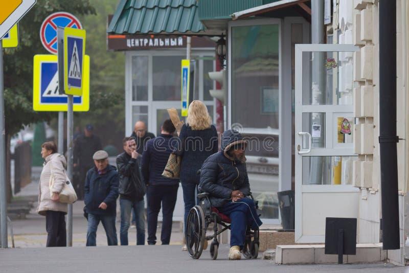 喀山,俄罗斯- 2017年9月9日:残疾有轮椅的叫化子贫困者在Ostrovskogo街道上请求金钱 免版税库存照片