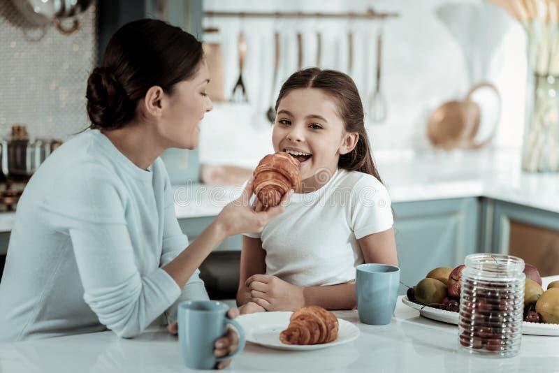 喂养一个孩子用新月形面包的仔细的母亲 库存图片
