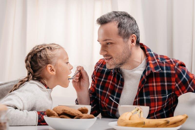 喂养可爱的女孩的微笑的父亲 免版税库存照片