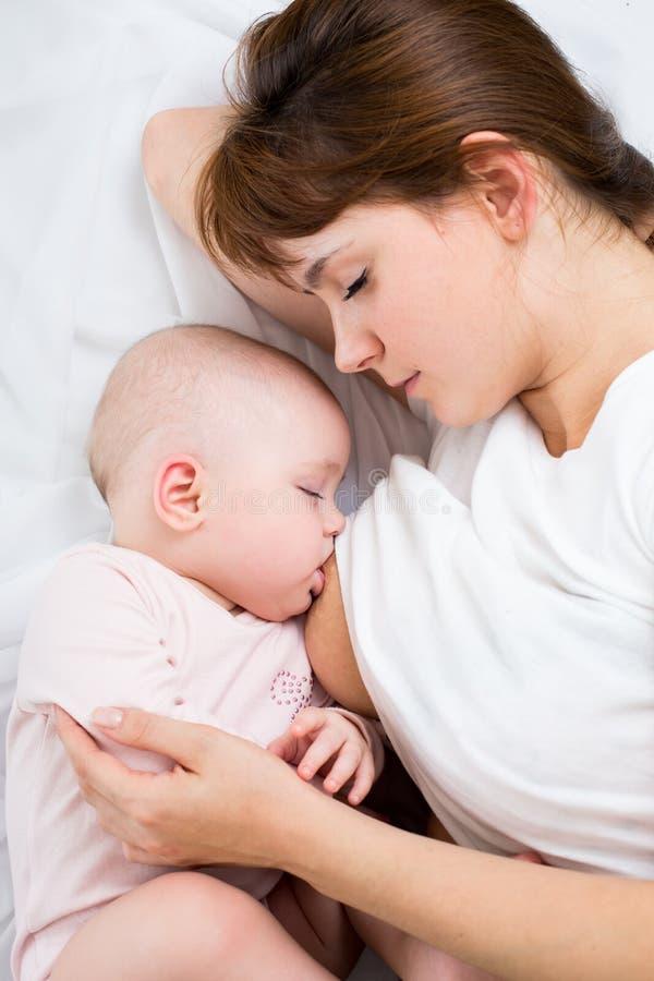 喂养她的女婴的轻松的母亲乳房 库存照片