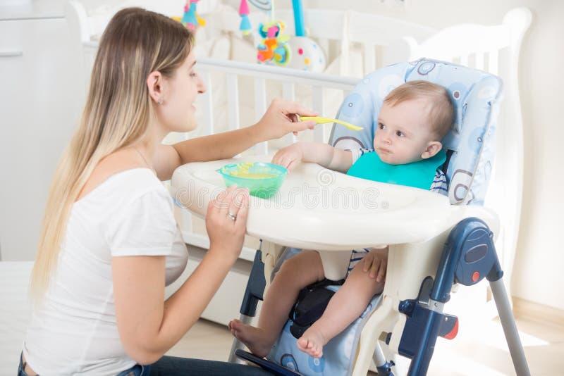 喂养她的小儿子的年轻母亲画象坐在高脚椅子 免版税库存图片