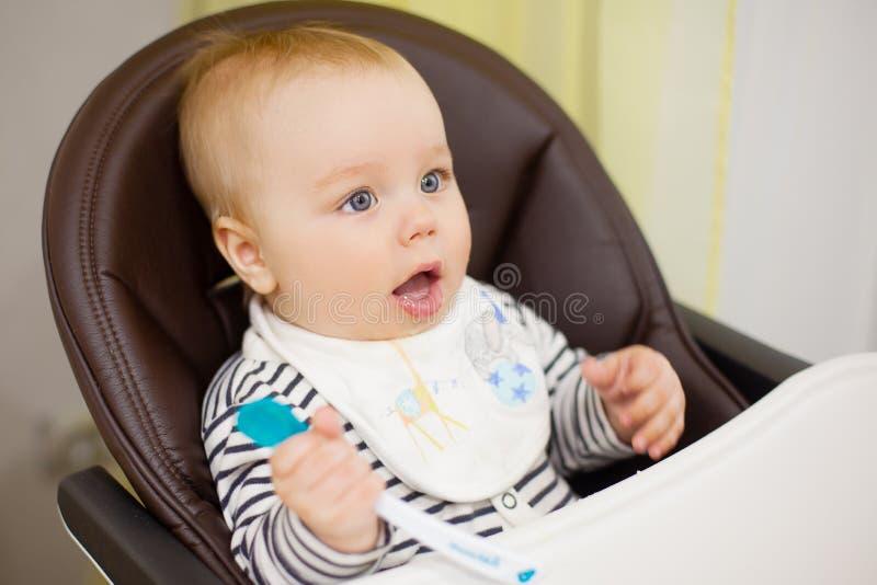 喂养她的小小儿子用粥的年轻母亲,坐在哺养的高婴孩椅子 免版税库存照片