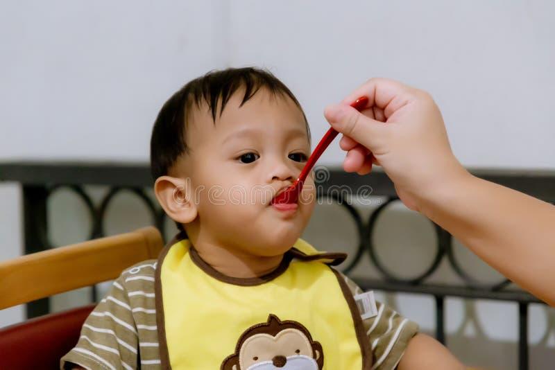 喂养她的有匙子的母亲婴孩 在家给健康食品的母亲她可爱的孩子 免版税库存照片