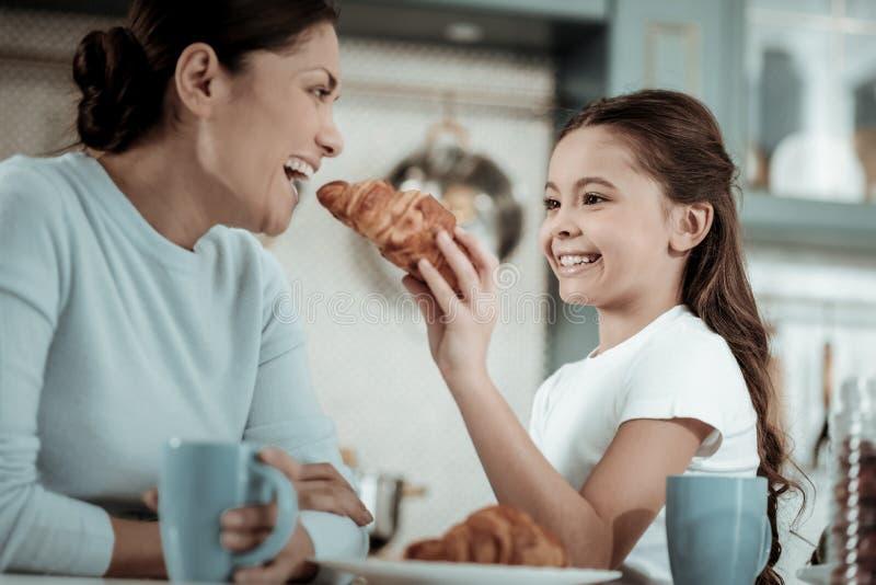 喂养她的母亲用新月形面包的小孩 库存图片