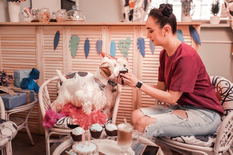 喂养她的狗用杯形蛋糕的妇女佩带的牛仔裤 免版税库存照片