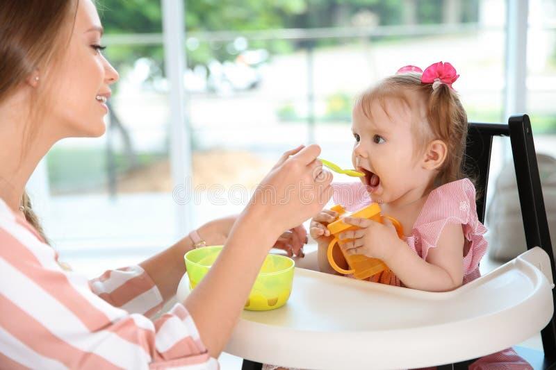 喂养她逗人喜爱的矮小的婴孩的有同情心的母亲 库存照片