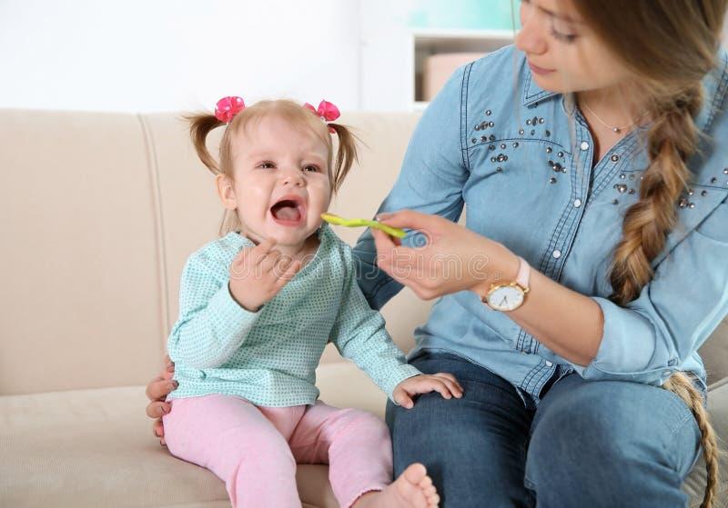 喂养她逗人喜爱的矮小的婴孩的有同情心的母亲 免版税库存图片