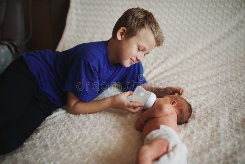 喂养有瓶的男孩新出生的婴孩牛奶 库存照片