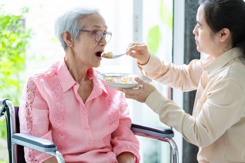 喂养资深妇女或母亲轮椅的年轻女性照料者或女儿在退休房子或家,亚裔年长患者 免版税图库摄影
