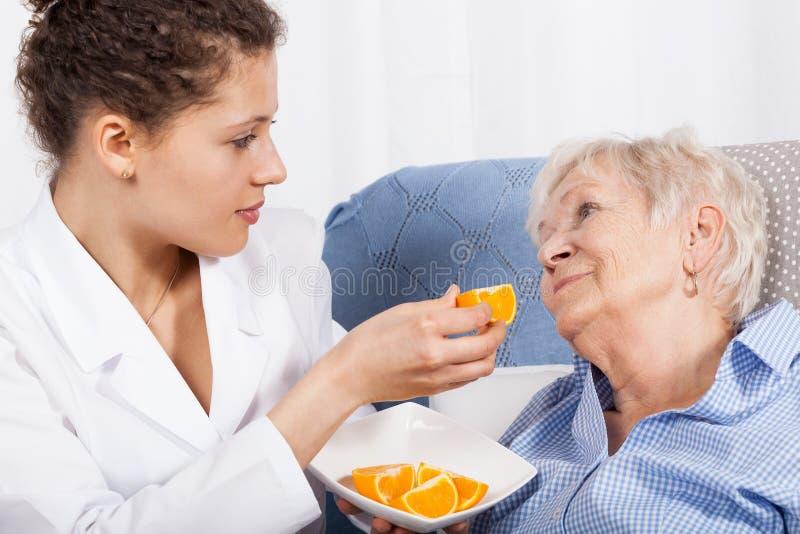 喂养一名年长妇女的护士 免版税库存图片