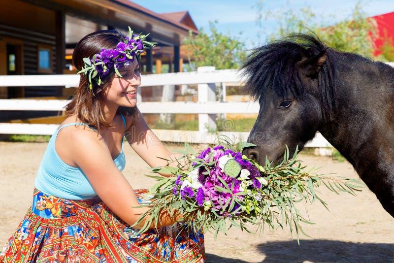 喂养在农场的美丽的女孩秸杆小马 免版税库存图片