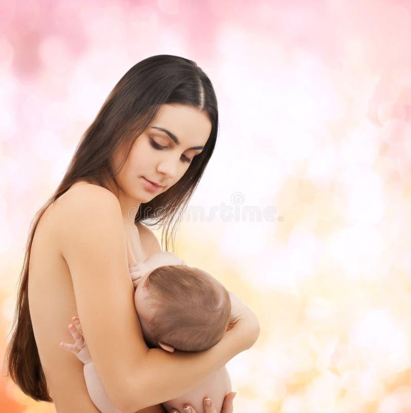 喂养她可爱的婴孩的愉快的母亲 库存照片