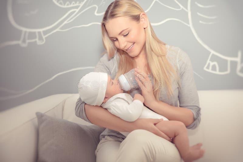 喂养她的母亲的婴孩 免版税库存图片