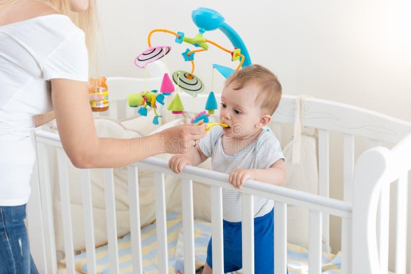 喂养她的婴孩用粥的年轻母亲在床上 库存图片