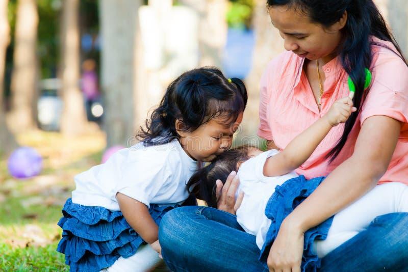 喂养她的婴孩的年轻母亲在公园 免版税图库摄影