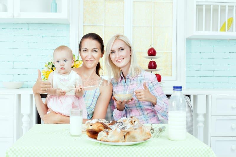 喂养孩子的两名妇女 免版税库存照片