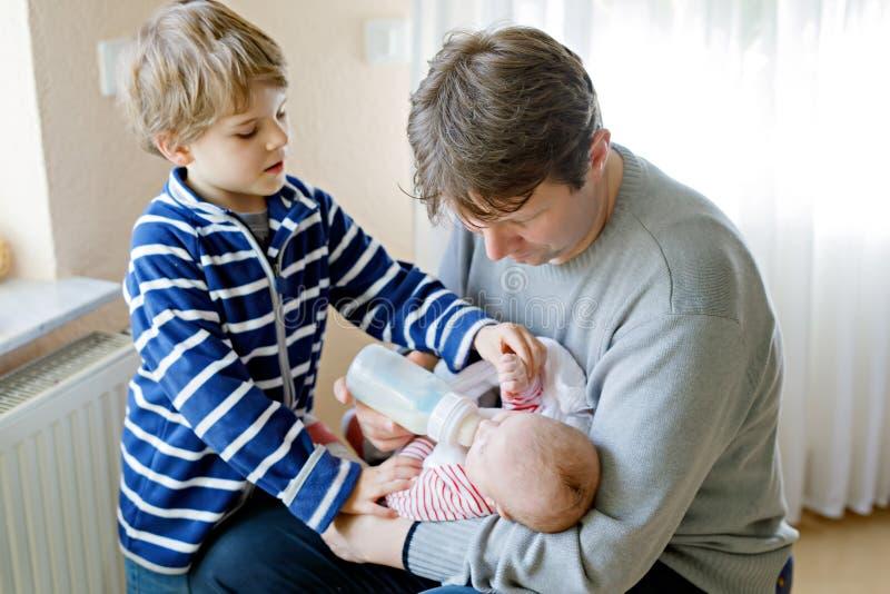 喂养新出生的小女儿用在奶瓶的牛奶的父亲和孩子男孩 免版税库存图片