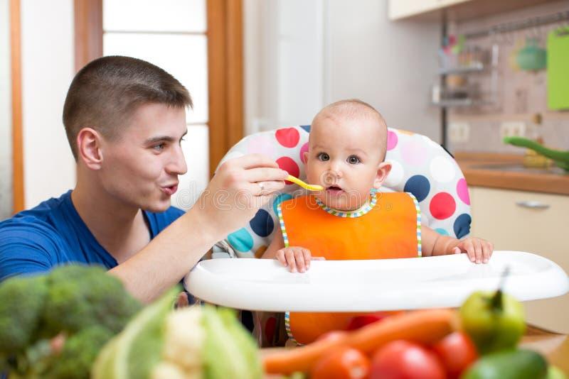 喂养他的婴孩的年轻爸爸在厨房 库存图片
