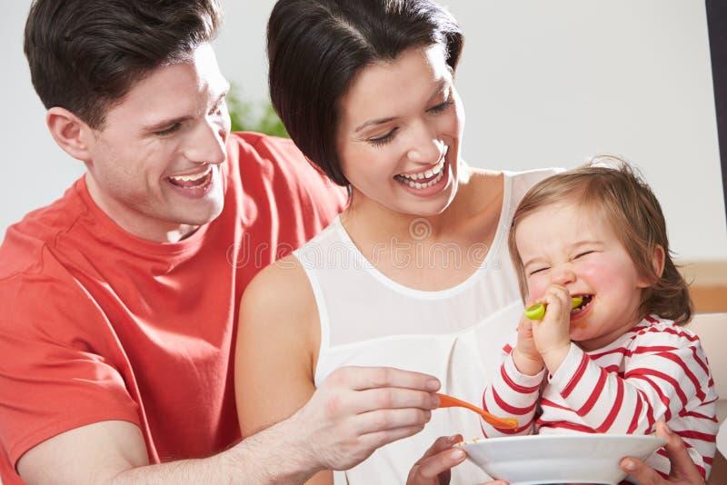 喂养从碗的父母小女儿 免版税图库摄影