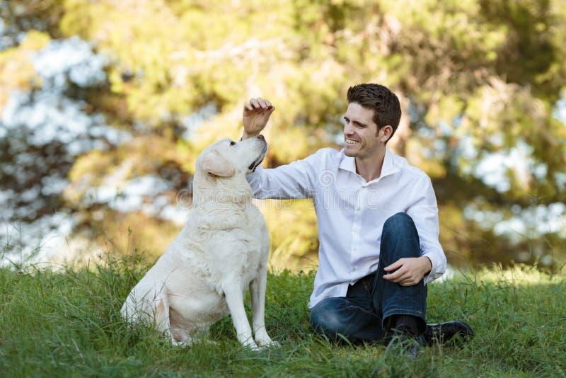 喂养非常老狗的年轻人户外 免版税库存图片
