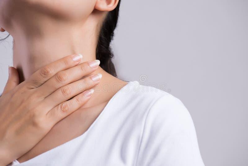 喉咙痛 接触她不适的脖子的美好的年轻女人手特写镜头  E 免版税库存图片