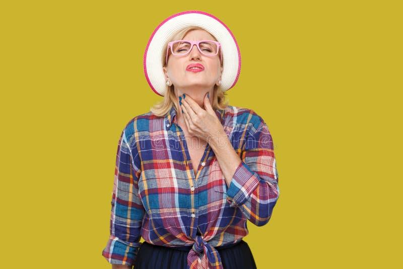 喉头痛苦病症或流感 病的现代时髦的成熟妇女画象便装样式的与帽子和镜片身分和 免版税库存图片