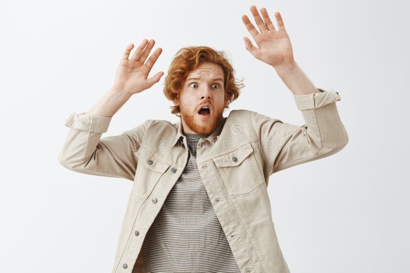 喘气与张的嘴的恐慌的害怕不安全的红头发人人看起来高正确的担心和上升的棕榈  免版税库存图片